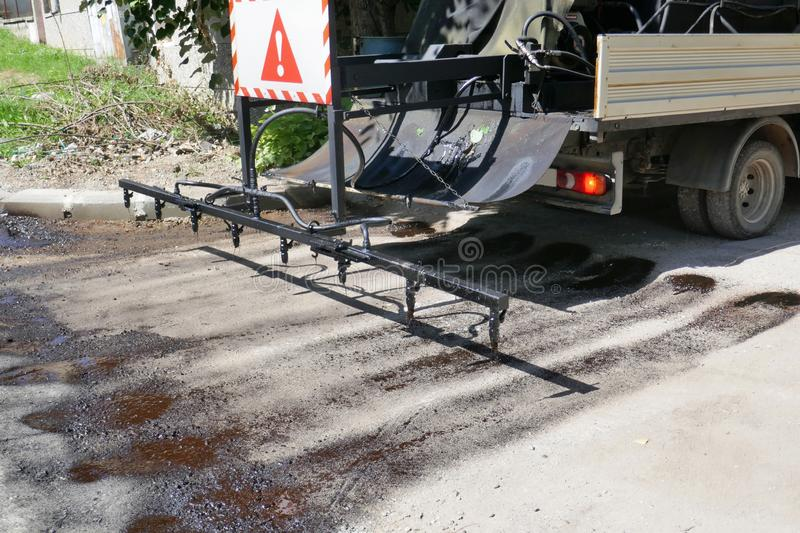 Oil spreader truck applying tack coats spraying bitumen emulsion with  spray lance before applying a new layer. Of asphalt royalty free stock photos