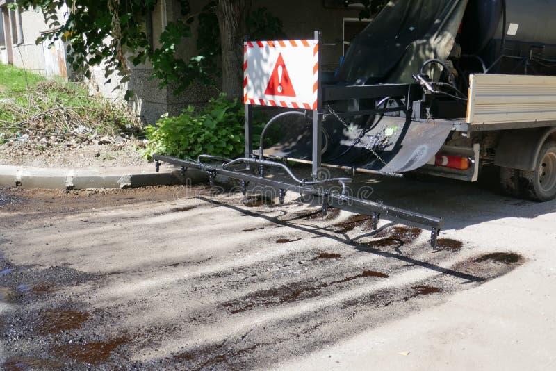 Oil spreader truck applying tack coats spraying bitumen emulsion with  spray lance before applying a new layer. Of asphalt stock photo