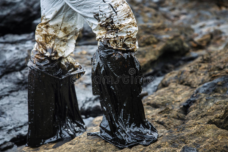 Oil stained plastic boots. Ao Prao Beach, Koh Samet, Rayong, Thailand - July 29, 2013: Gulf oil spill is shown on the rock on July 31, 2013 in Ao Prao Beach, Koh royalty free stock image