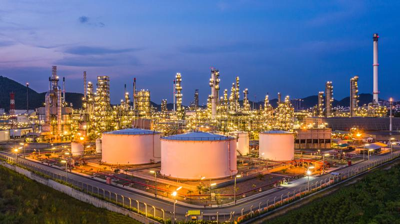 Oil storage tank with oil refinery plant background at twilight, Aerial view oil refinery, refinery plant, refinery factory and. Petrochemical plant stock photo