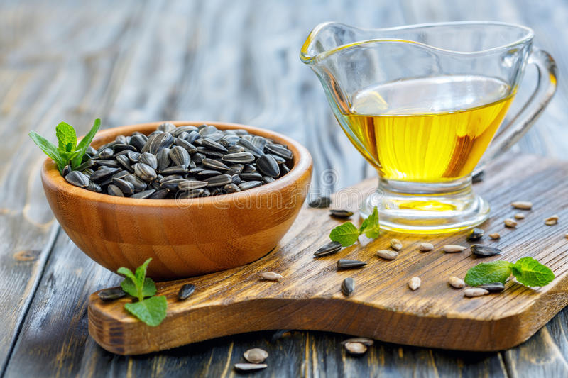 Oil and sunflower seeds in a wooden bowl. Oil and sunflower seeds in a bowl over old wooden table, selective focus stock photo