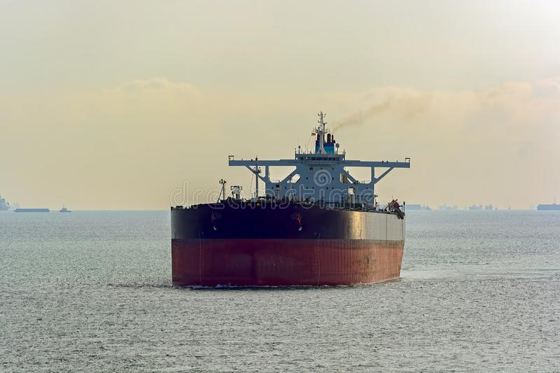 Oil supertanker in Singapore Strait. Front view of crude oil tanker in the ballast underway in sea strait at sunset royalty free stock photos
