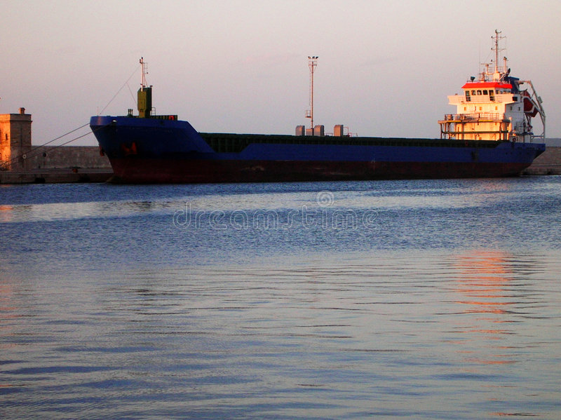 Oil tanker. A black oil tanker in Piombino harbour - Italy - At the sunset time stock image