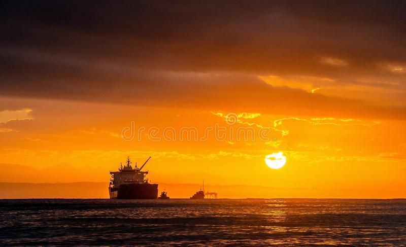 Oil tankers ship at sea on a background of sunset sky. stock photo