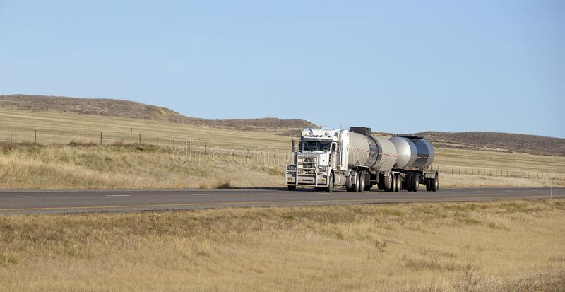 Oil transport semi truck. Oil semi truck with white trailer driving on highway stock photography