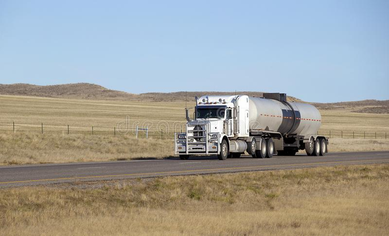 Oil transport semi truck. Oil semi truck with white trailer driving on highway royalty free stock photography
