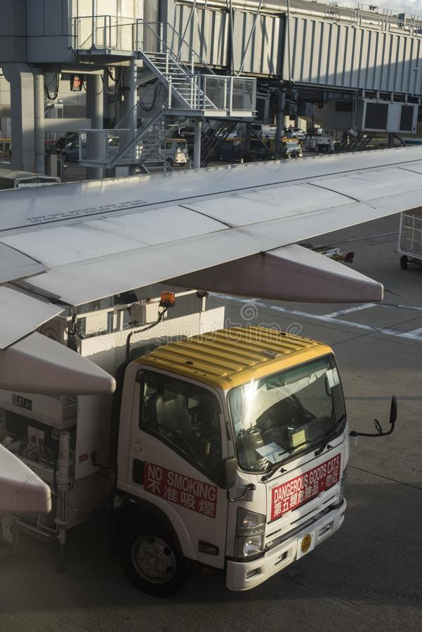 Oil truck is refueling an airplane before take off at Hong Kong airport. stock photography