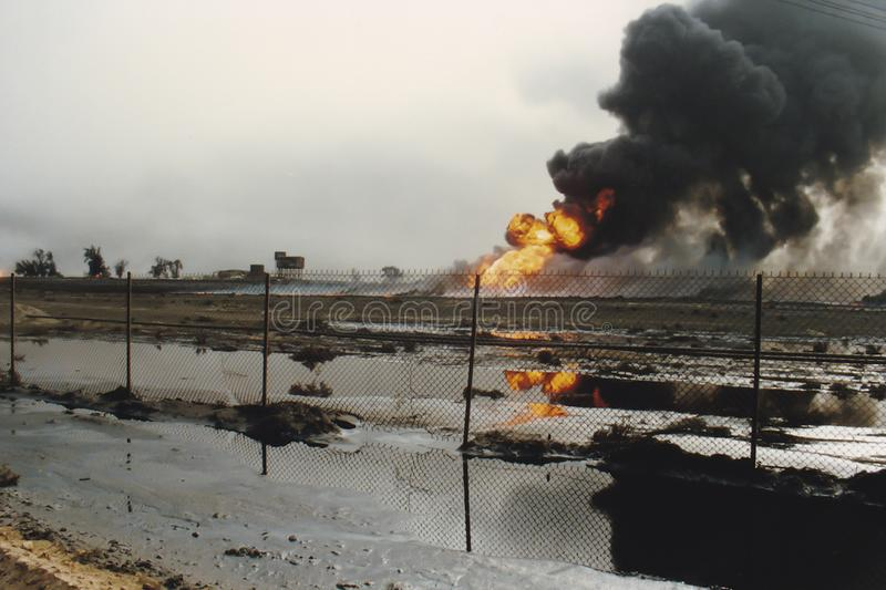Oil well burning in field of oil slick, Kuwait stock photography