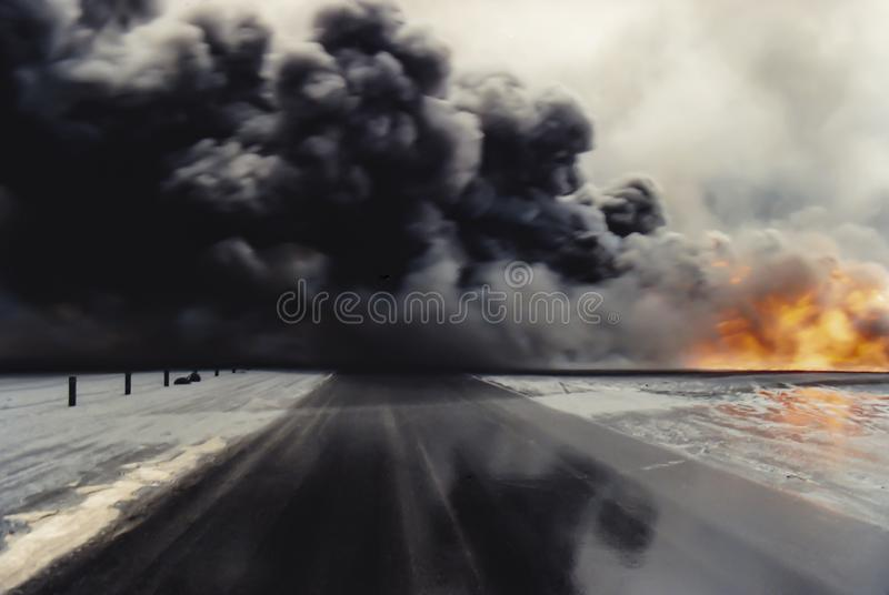 Oil well fires after Desert Storm Persian Gulf War. Kuwait City, Kuwait - circa April 1991 : Oil well fires in fields with oil slick road in aftermath of Desert royalty free stock photo