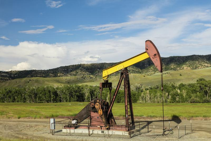 Oil well pump mountains forest royalty free stock photos