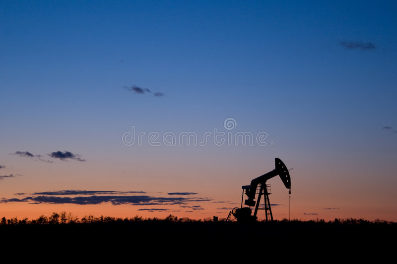 Oil well pumpjack sunset silhouette royalty free stock images