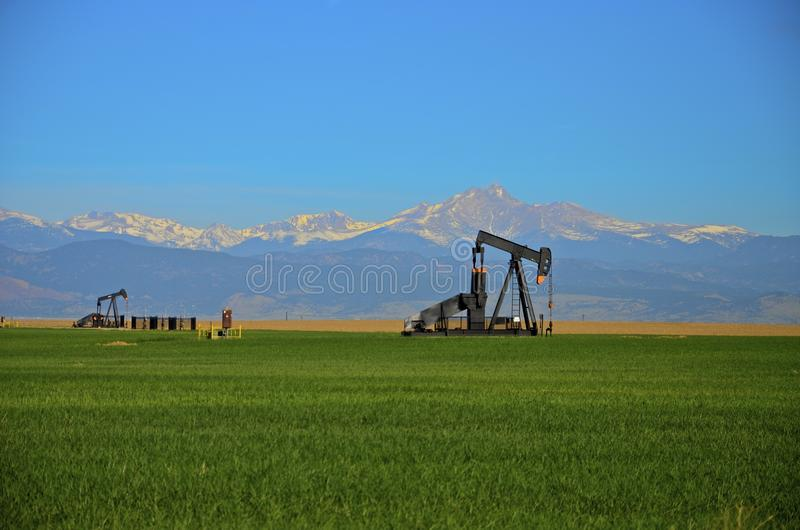 Oil Wells, Pump Jack , corn field and Mountains stock photography