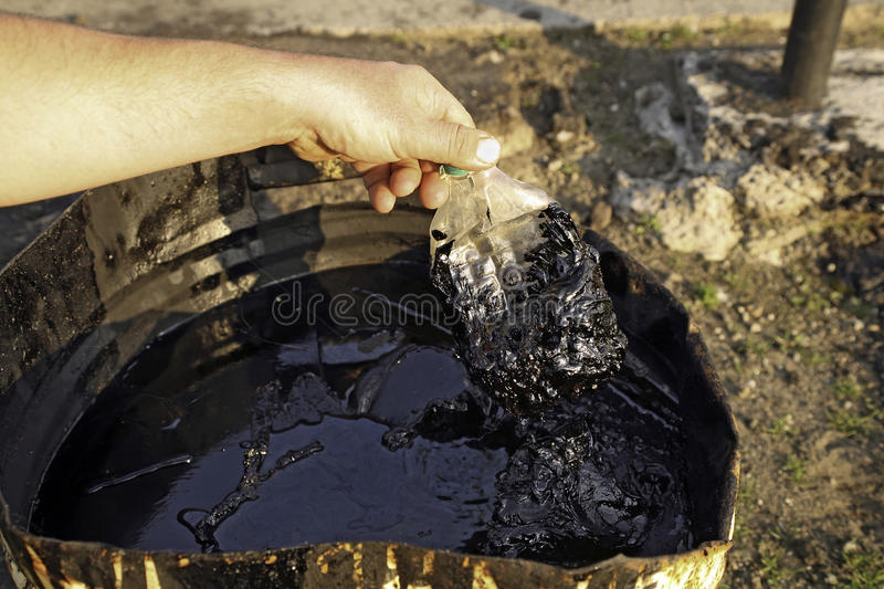 Oil wells with polluted ground. Hand with greasy plastic bottle stock photography