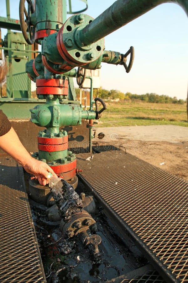 Oil wells with polluted ground. Hand with greasy plastic bottle stock photos