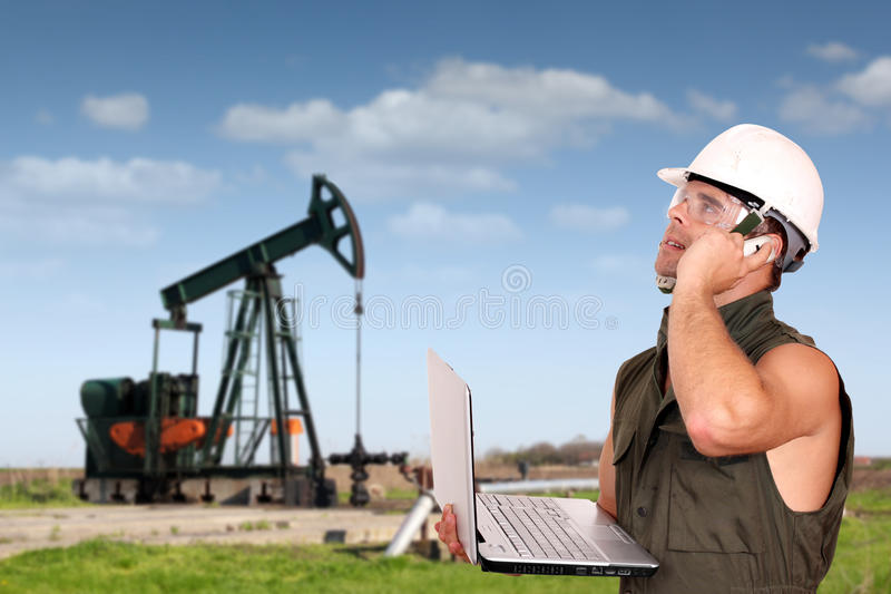 Oil worker. With laptop and phone royalty free stock image