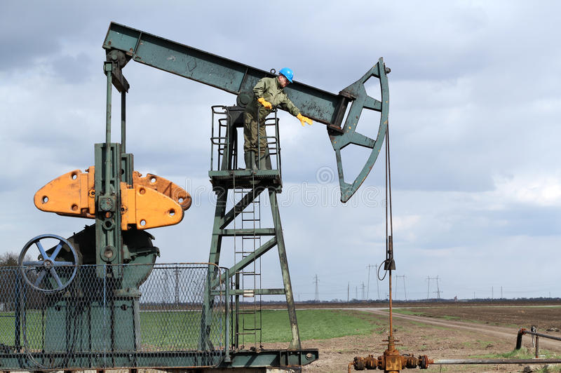 Oil worker. Standing at pump jack royalty free stock images
