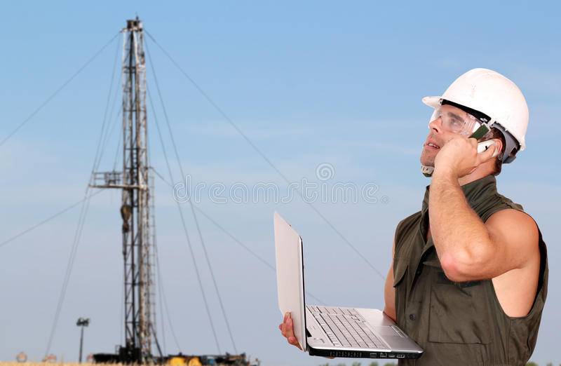 Oil worker. With laptop and rig stock photo