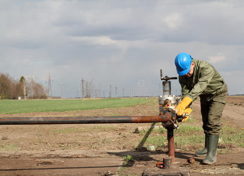 Oil worker. Closes the valve stock image