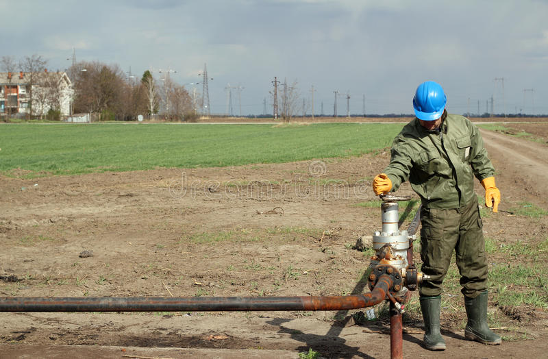 Oil worker. Open pipeline valve royalty free stock images