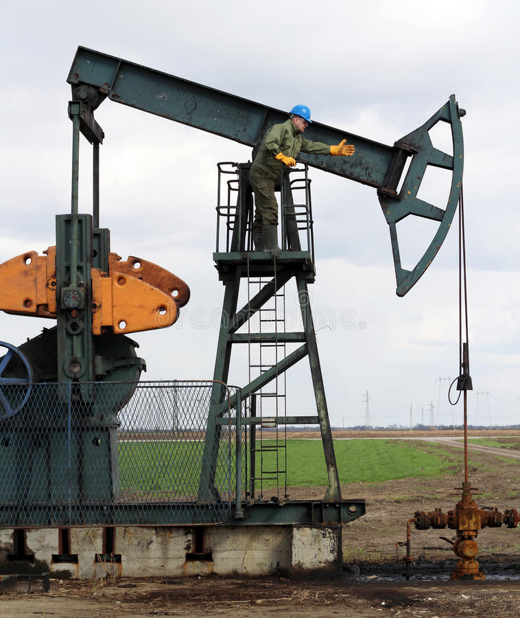 Oil worker. And pump jack royalty free stock image