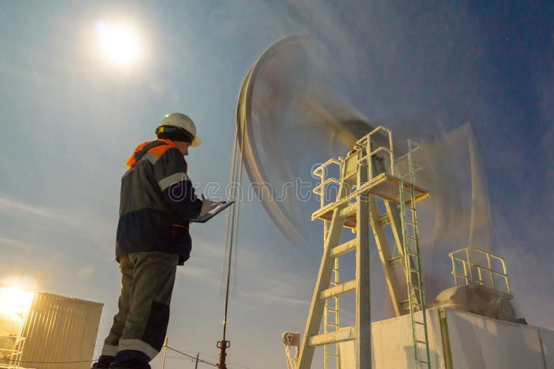 Oil worker check oil pump. Oil Drill, field pump jack with snow storm and worker.  Fossil Energy Resource Concept. Oil worker check oil pump. Oil Drill, field royalty free stock image