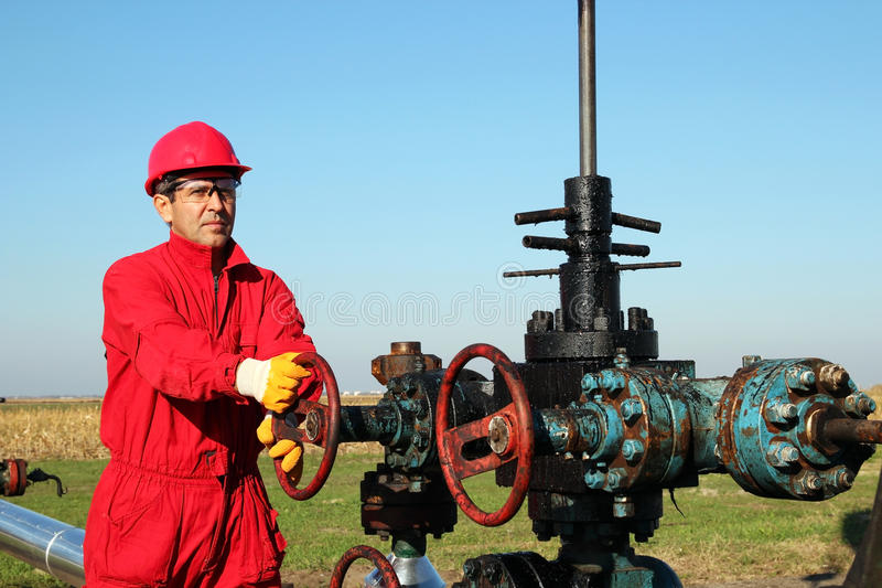 Oil Worker at Drilling Rig. Oil worker turning valve on oil rig stock photography