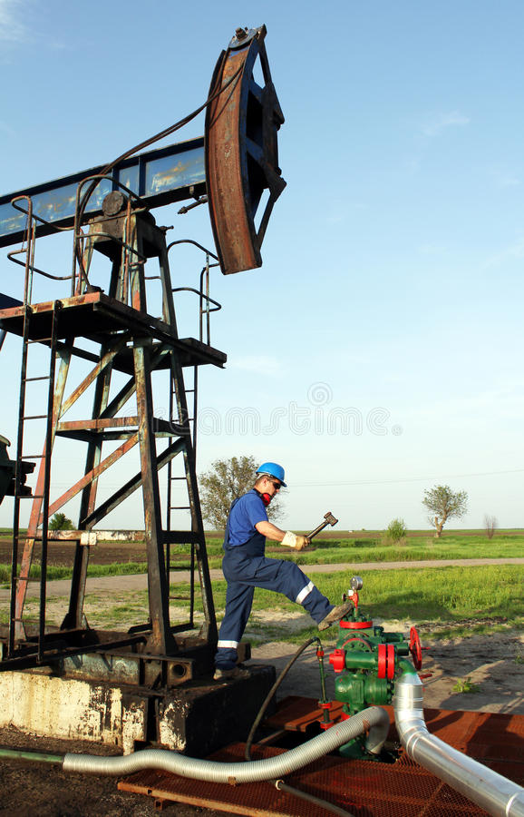 Oil worker with hammer. On oilfield stock photos