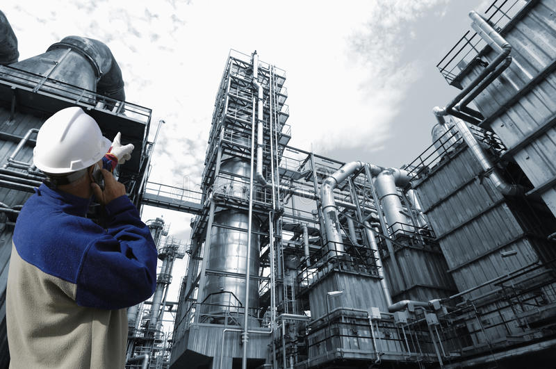 Oil worker and industry plant. Oil-worker, engineer, pointing at large refinery exterior stock photos