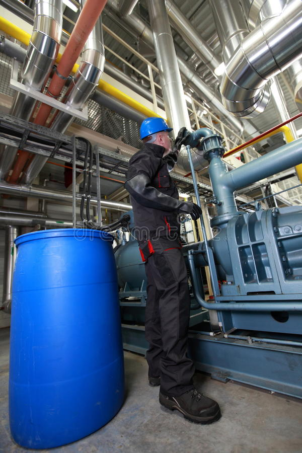 Oil Worker inside refinery. Oil Worker in helmet and uniform, inside refinery checking system stock photo