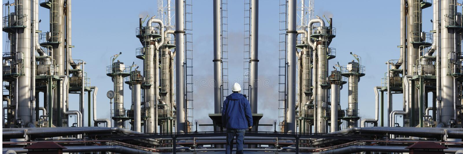 Oil worker and oil refinery industry. Oil and gas worker standing in front of large refinery installation, panoramic perspective royalty free stock photography