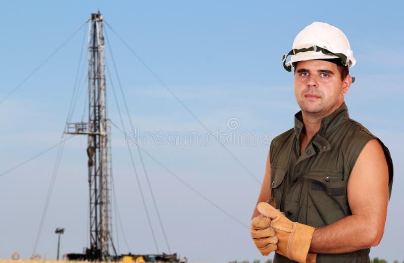 Oil worker on oilfield. Oil worker posing on oilfield royalty free stock image