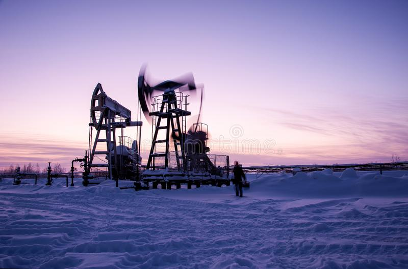 Oil worker in oilfield. Pump jack and engineer on a winter sunset sky background. Western Siberia. stock images