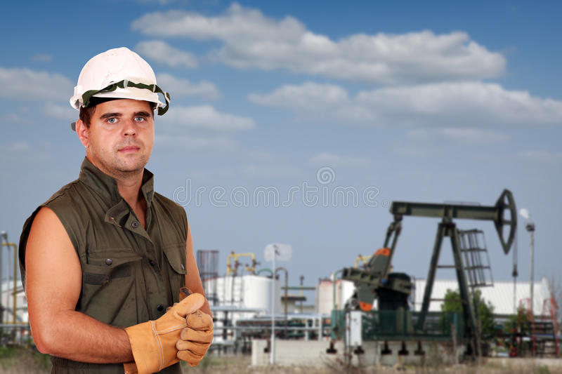 Oil worker on oilfield. With refinery stock photo
