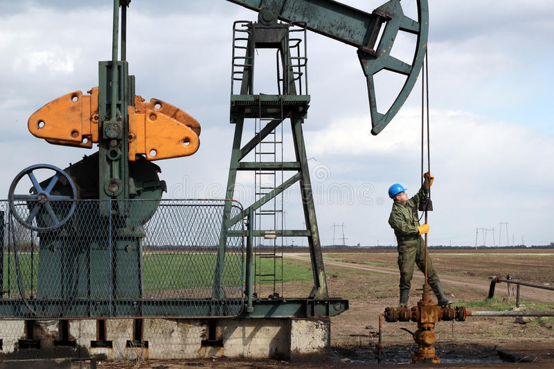 Oil worker standing at pipeline. And check pump jack stock photo