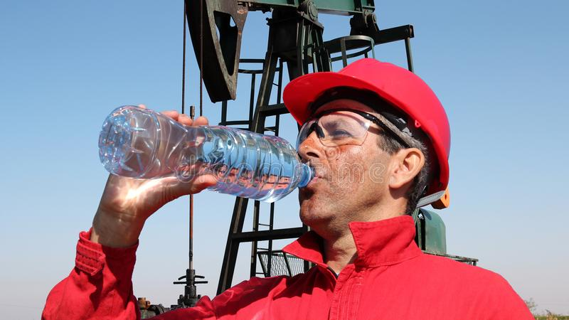 Oil Worker Taking Break And Drinking Fresh Water. Thirsty oil worker with personal protective equipment drinking fresh water in front of oil well stock photography
