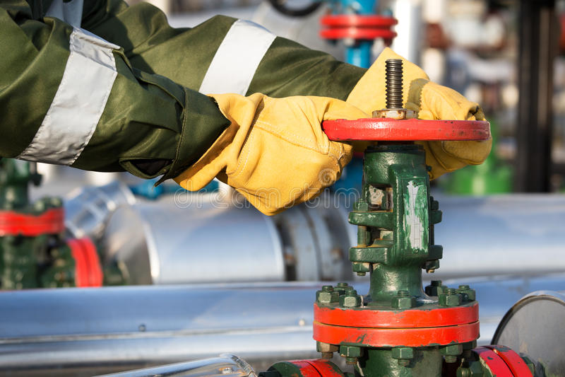 Oil worker turning valve. On the oil field stock photo