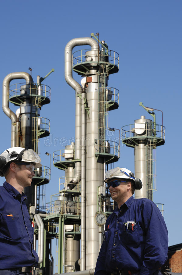 Oil workers and refinery. Two oil workers, engineers with refinery in background, pipelines and towers stock photo