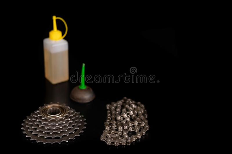 Oiling the bicycle chain with an oil can on the workshop table. Servicing of bicycle parts. Dark background, bike, close-up, closeup, derailleur, equipment royalty free stock photo