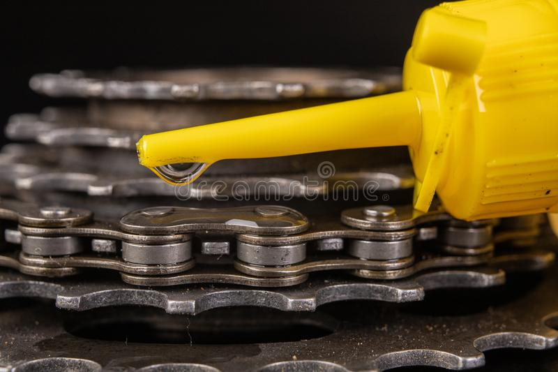 Oiling the bicycle chain with an oil can on the workshop table. Servicing of bicycle parts. Dark background, bike, close-up, closeup, derailleur, equipment stock photos