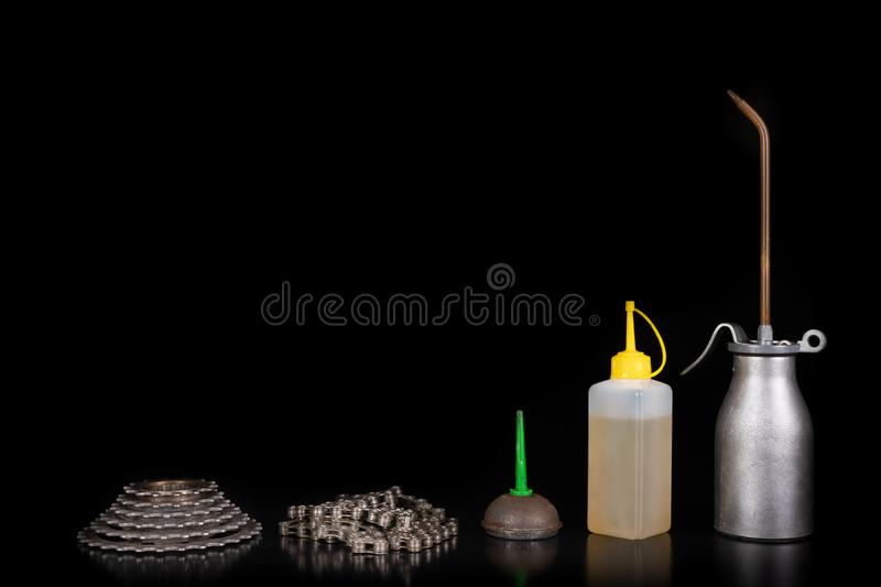 Oiling the bicycle chain with an oil can on the workshop table. Servicing of bicycle parts. Dark background, bike, close-up, closeup, derailleur, equipment royalty free stock image