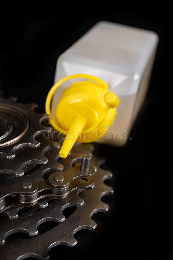Oiling the bicycle chain with an oil can on the workshop table. Servicing of bicycle parts. Dark background, bike, close-up, closeup, derailleur, equipment stock photo