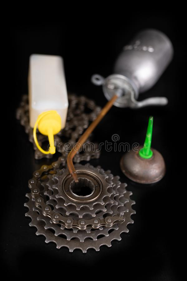 Oiling the bicycle chain with an oil can on the workshop table. Servicing of bicycle parts. Dark background, bike, close-up, closeup, derailleur, equipment stock photography