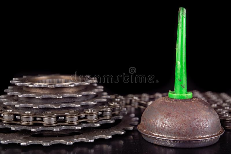 Oiling the bicycle chain with an oil can on the workshop table. Servicing of bicycle parts. Dark background, bike, close-up, closeup, derailleur, equipment royalty free stock photography