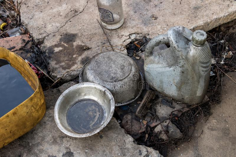 Oily Metal Bowls with Old Grey Plastic Diesel Oil Bottle on Dirty Floor - Recycling. Used Gray Diesel Oil Bottle with no Label - Dirty Greasy Aluminum Bowl on stock image