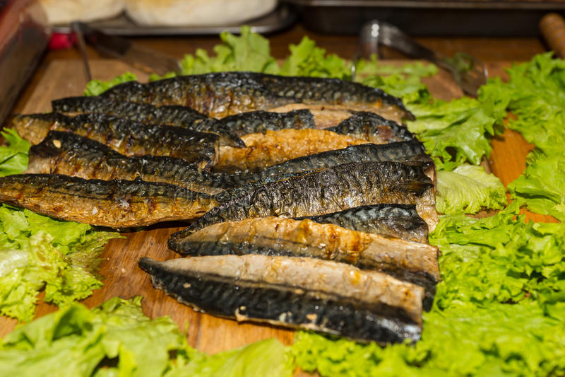 Oily Smoked Fish Filets with Lettuce Leaf Garnish stock photography