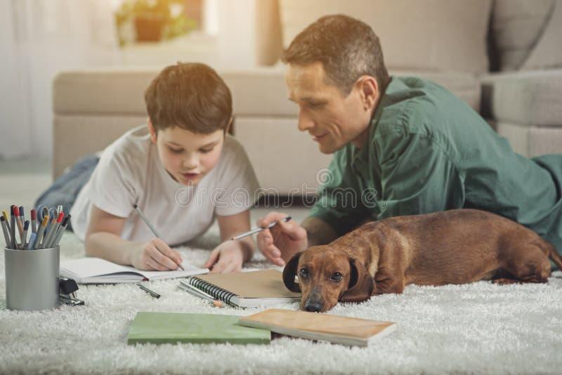 Ointresserad hund som ligger nära upptagen fader och son arkivbilder