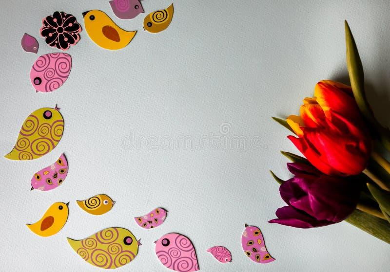 Oiseaux colorés de papier de ressort avec des tulipes sur le fond bleu de sucrerie L'origami fait main ouvre les oiseaux de papie photos stock