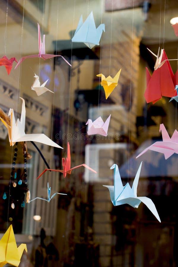 Oiseaux de papier colorés d'origami attachés aux ficelles image stock