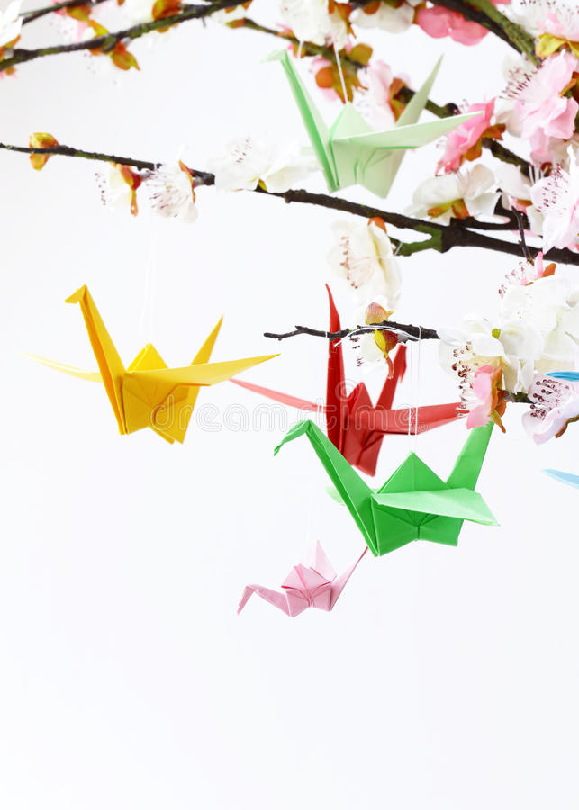 Oiseaux de papier colorés d'origami sur les branches fleurissantes de la cerise images libres de droits