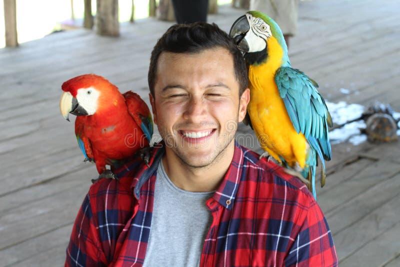 Oiseaux exotiques collant avec un homme photographie stock